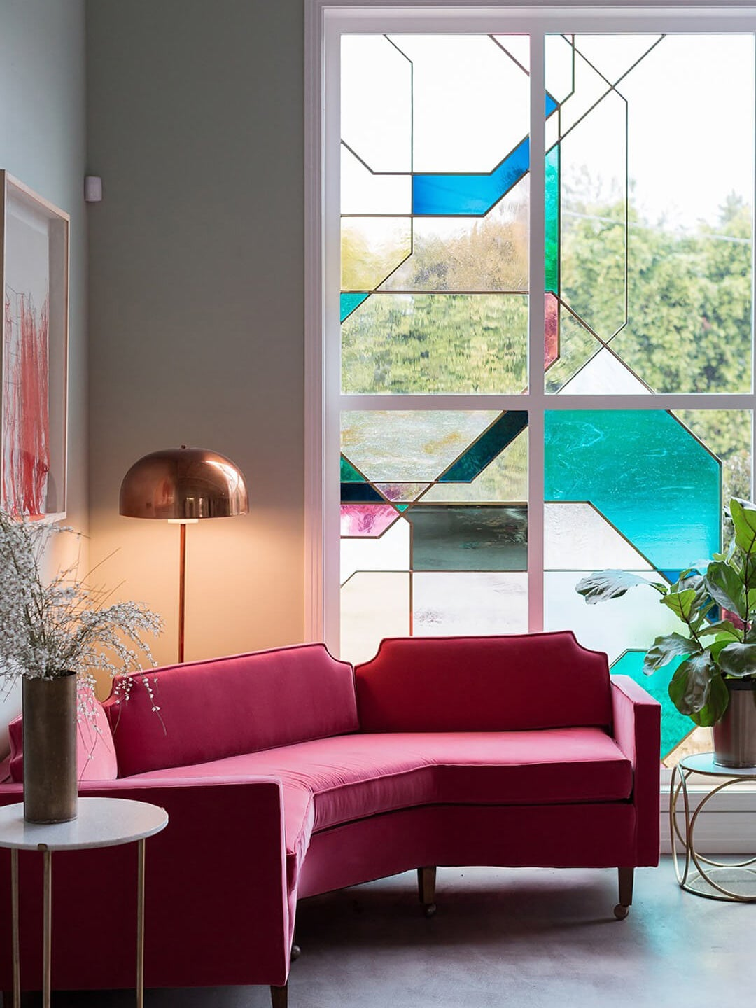 pink sofa in front of stained glass window