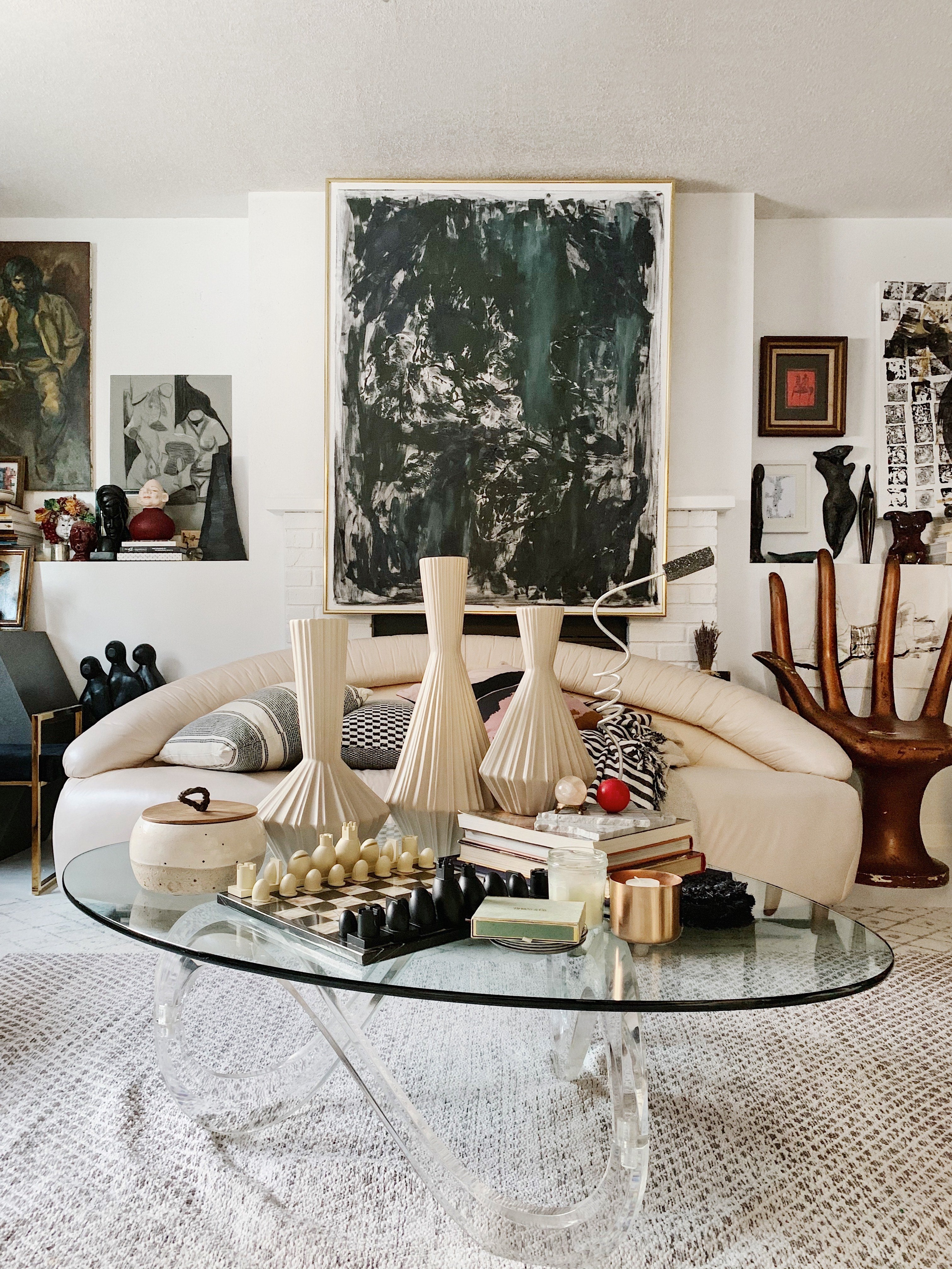 white retro sofa with glass coffee table with a lot of vases