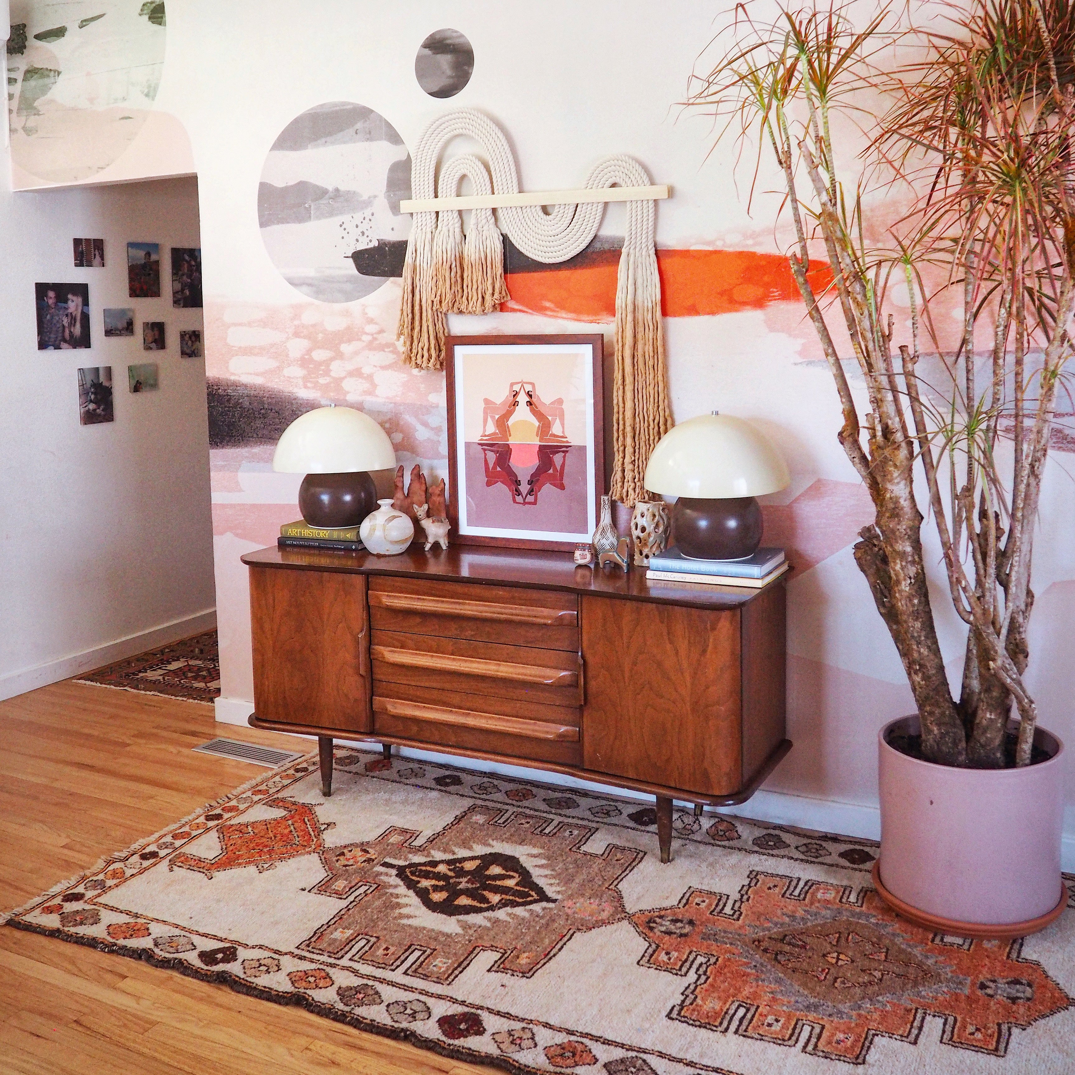 pink mural in a hallway with a mid century chest