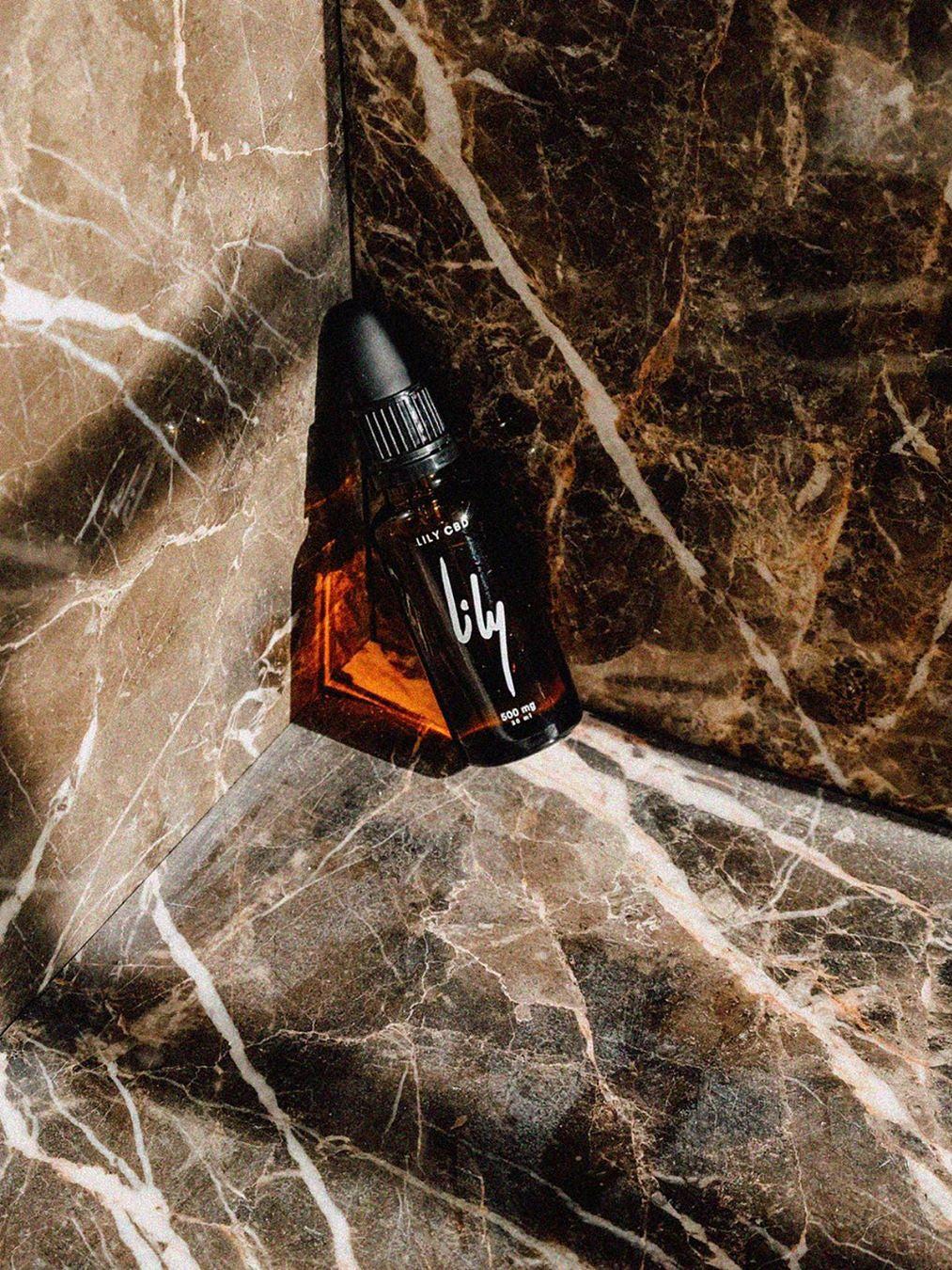 Vial of CBD oil against marble background