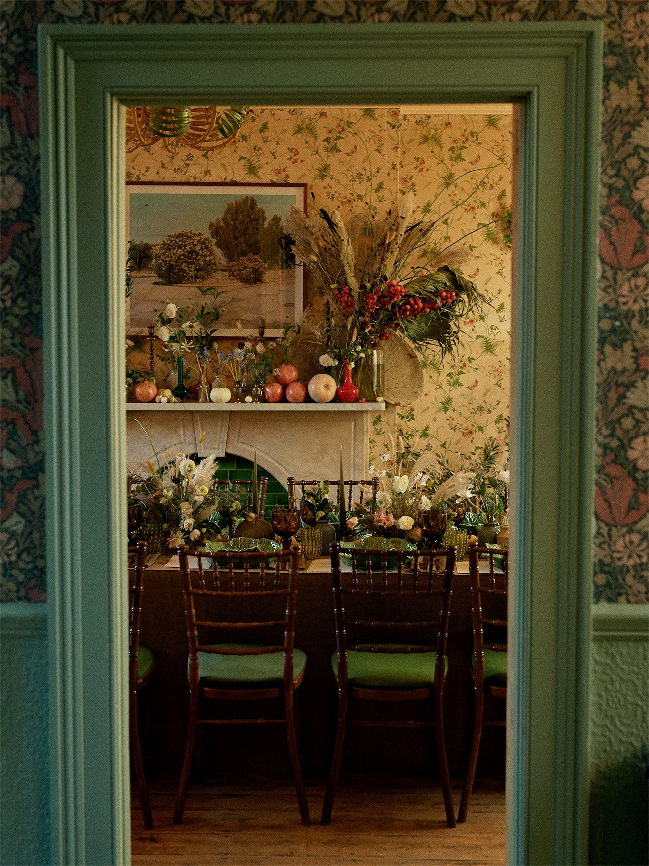 dining room with floral wallpaper and a lot of plants on the table