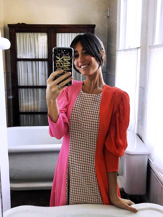 woman in red and pink dress taking mirror selfie