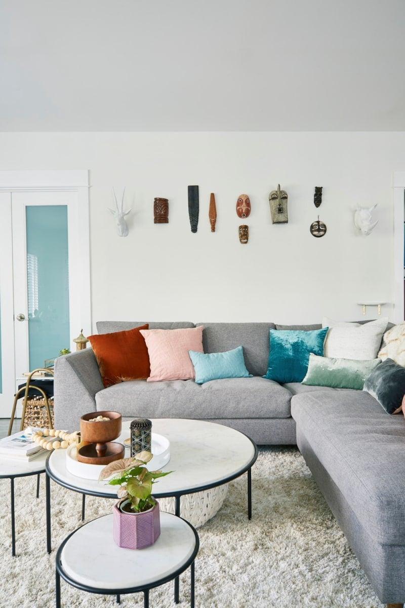 white living room with grey sofa and colorful throw pillows