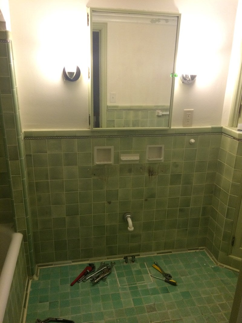 green tile bathroom without a sink or toilet
