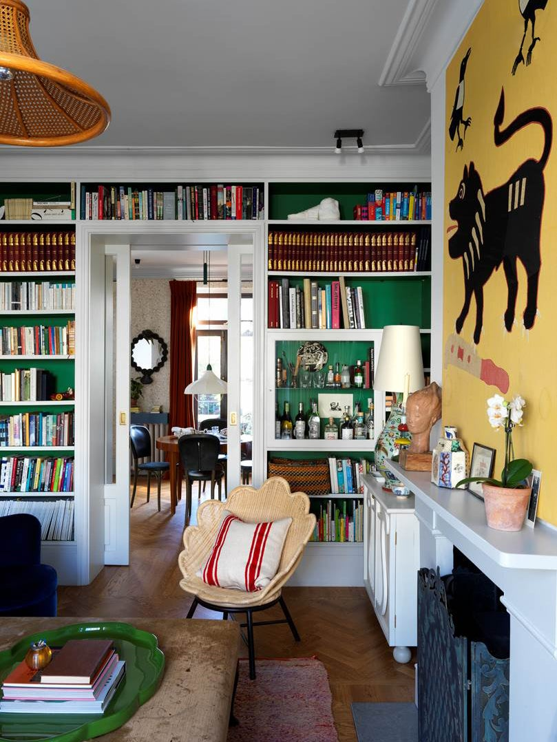 Living room with green bookcases and yellow art
