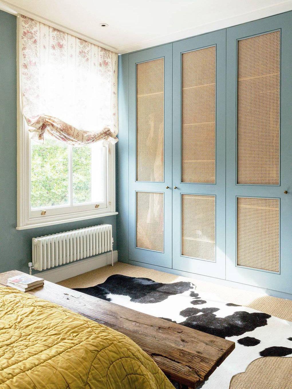 Bedroom wardrobes with cane doors and blue walls