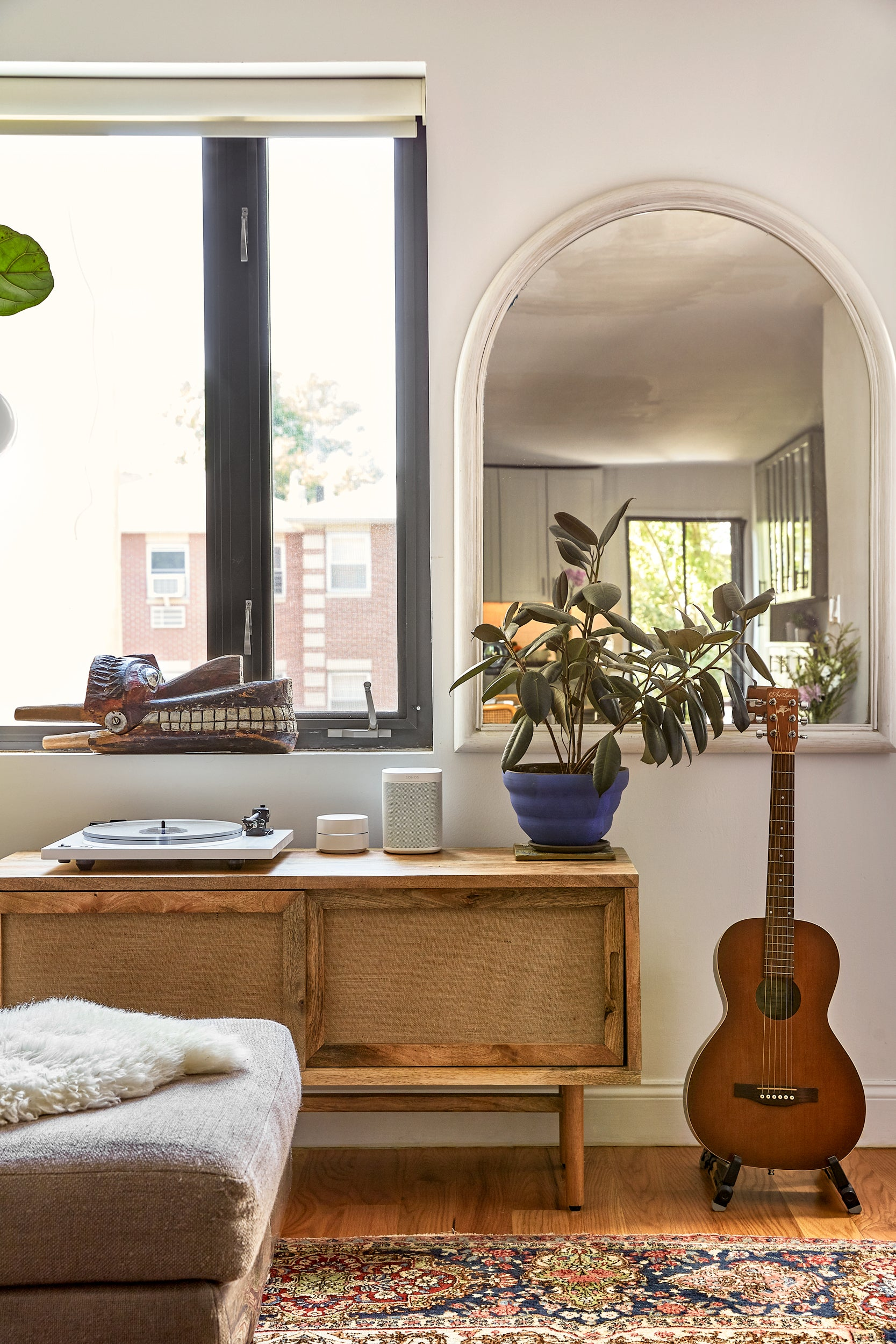 rattan console underneath mirror and guitar