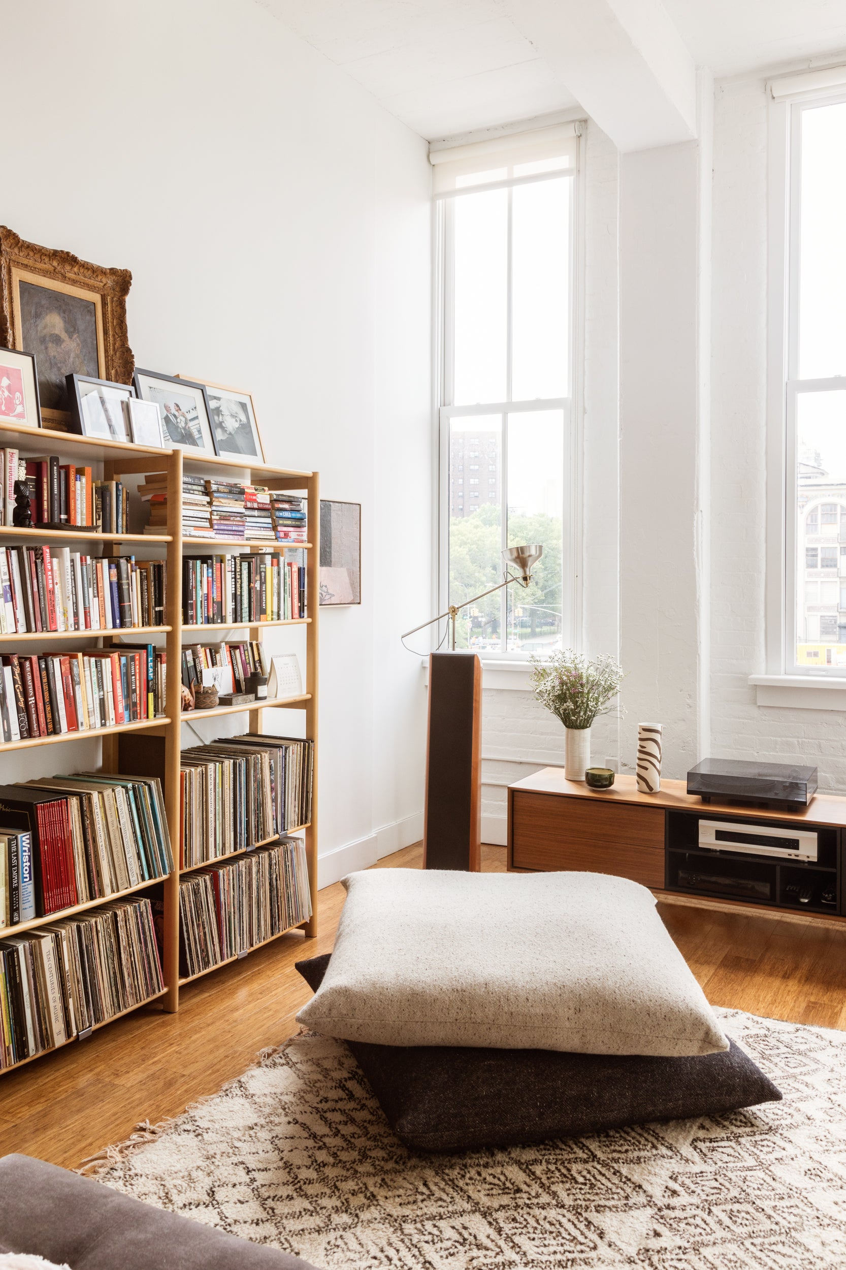 living room with bookcases and floor pillows