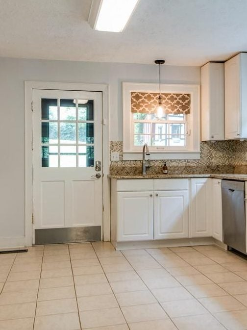 white farm door with white cabinets and dated tan floors