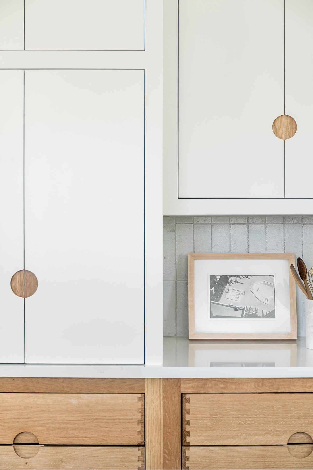 white cabinets with wood cut outs for handles