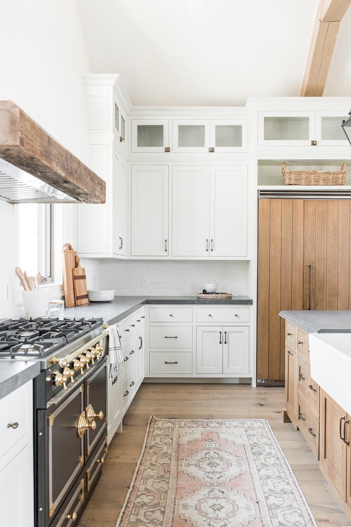 white kitchen with black range and wood detailing above the hood