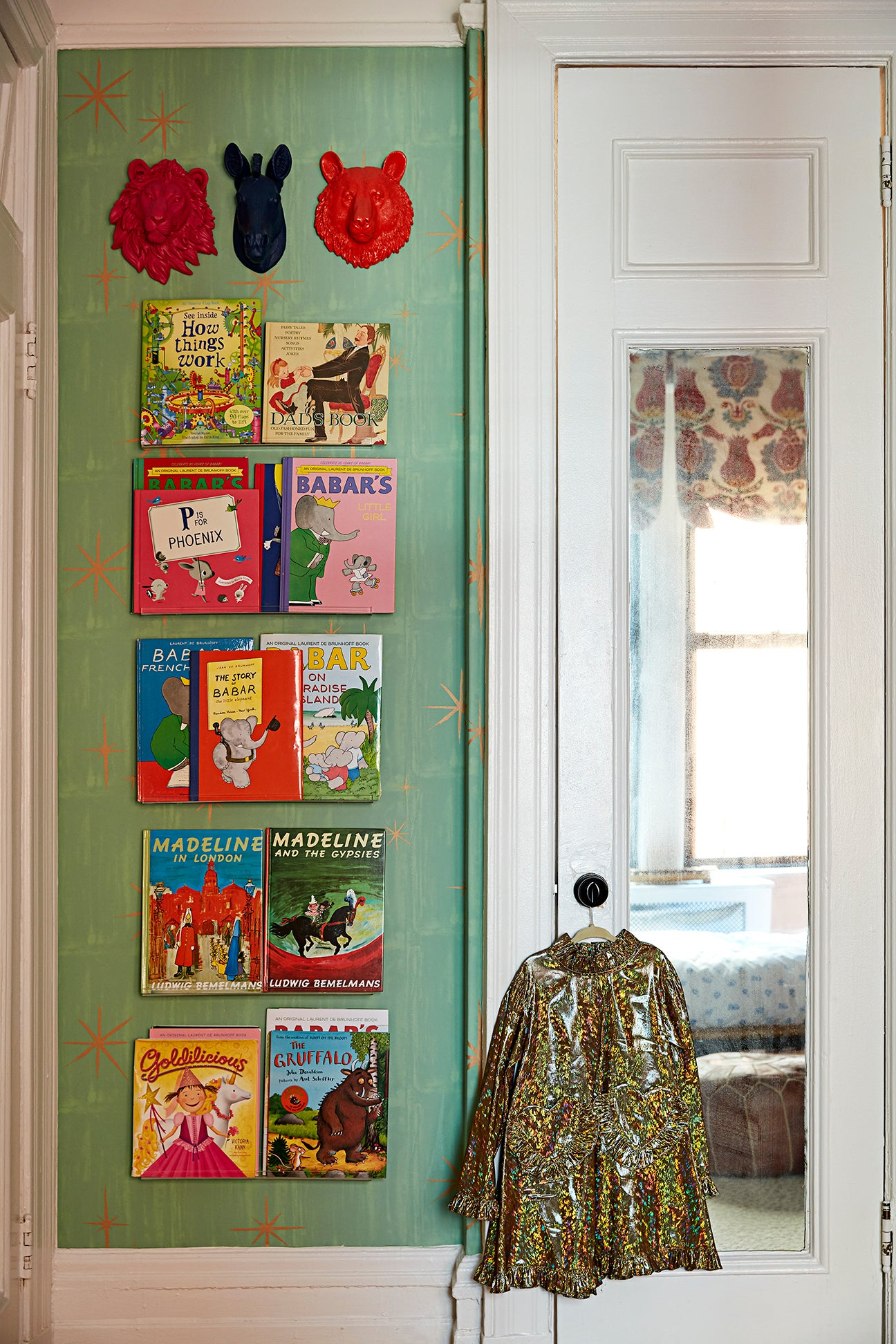 Kids room with starry green wallpaper and book shelves