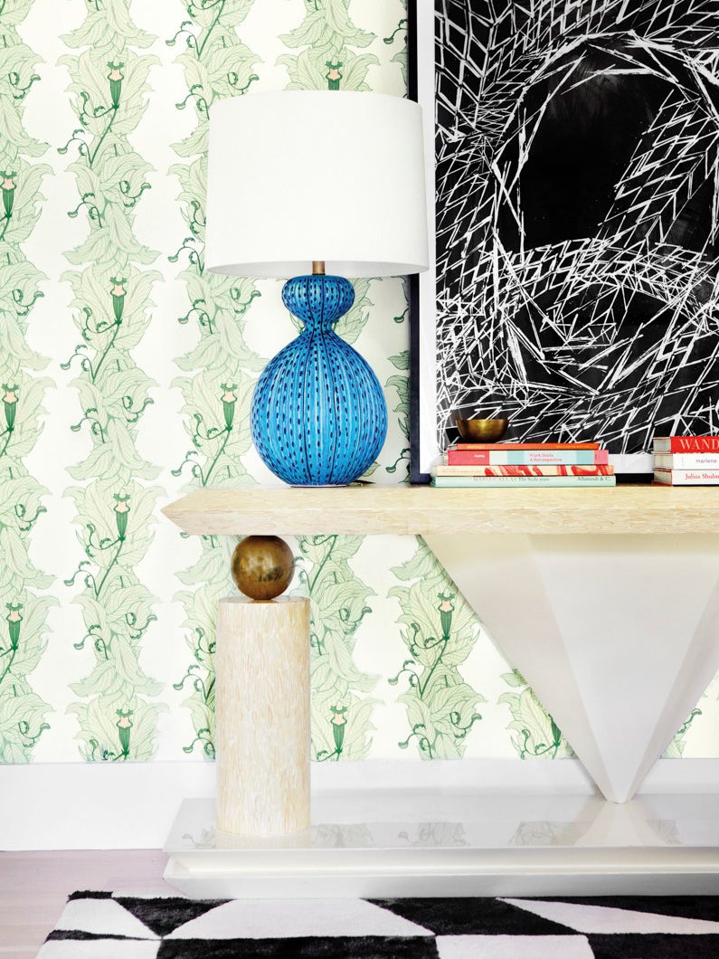 entryway with console table and green leaf wallpaper