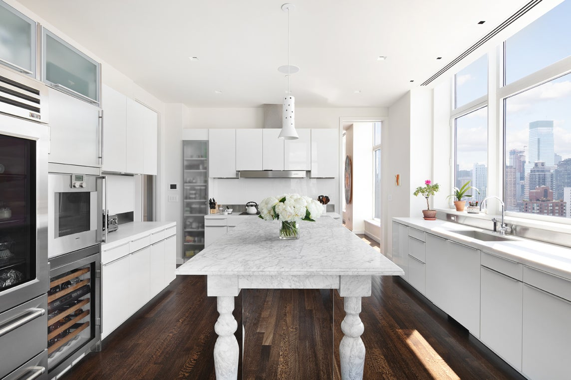 white kitchen with large table as the island