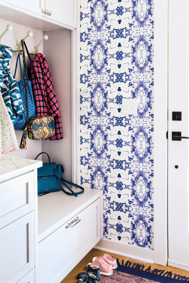 Entryway with blue and white graphic wallpaper and white closet