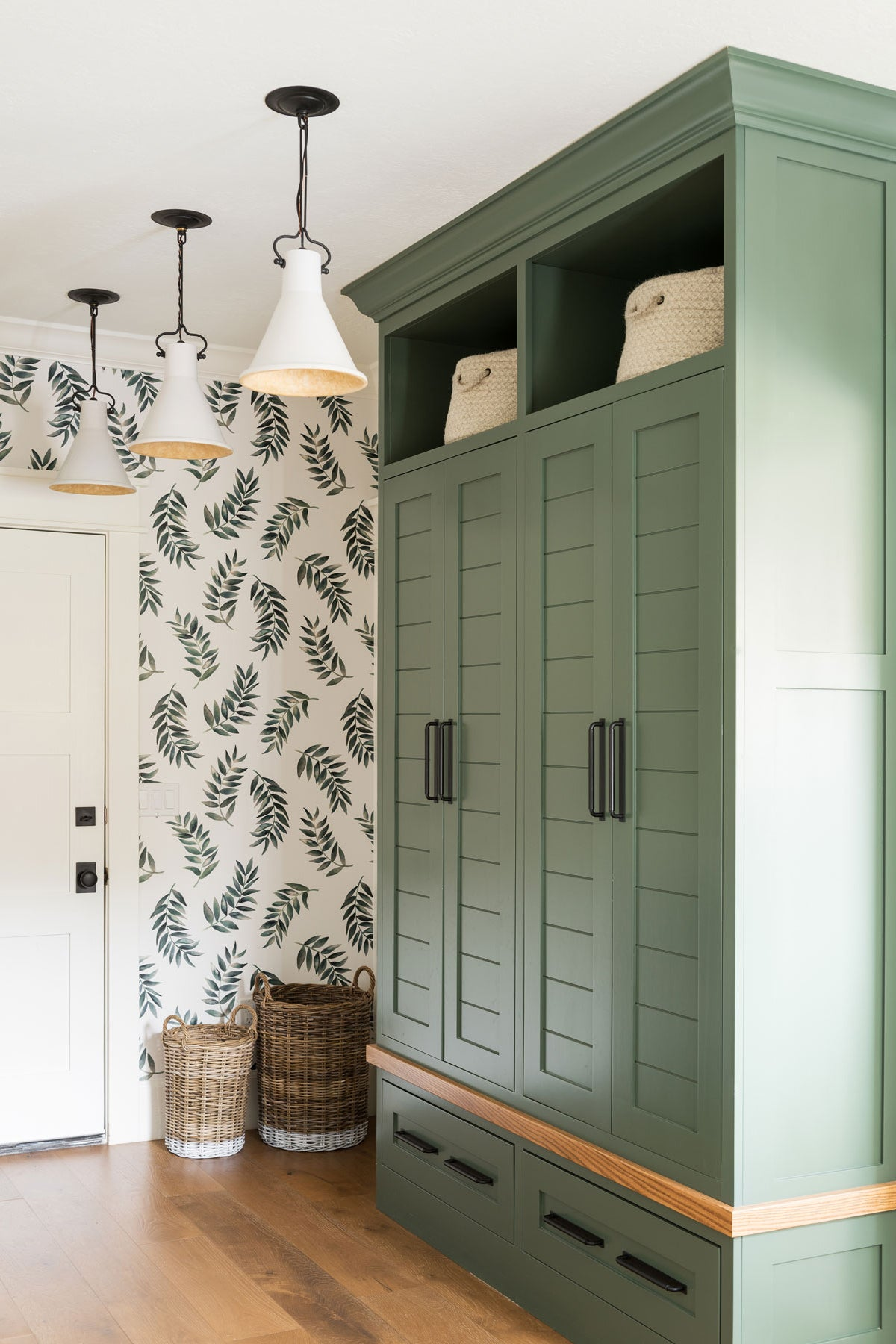 Entryway with leaf-print wall and green cabinet