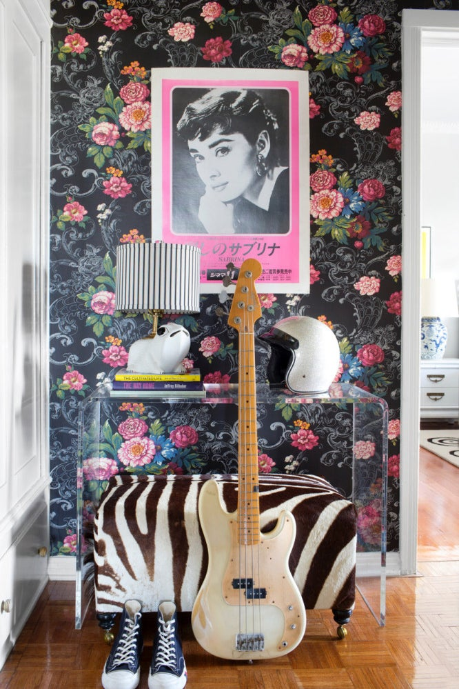 entryway with dark floral wallpaper and zebra print bench