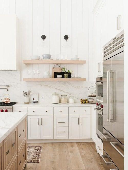 large white kitchen with steel fridge and wood island