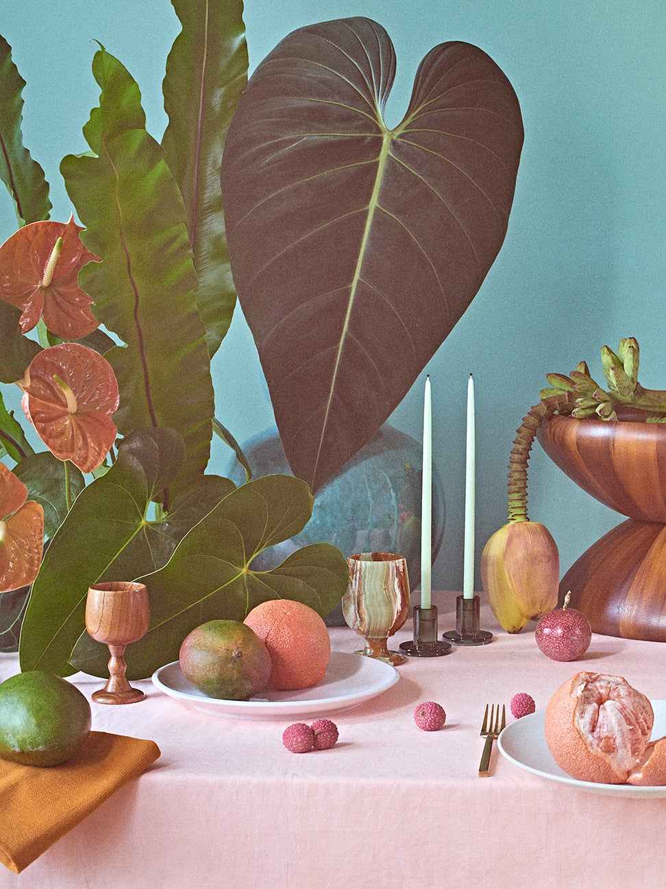 vignette with plants, candlesticks, and fruit