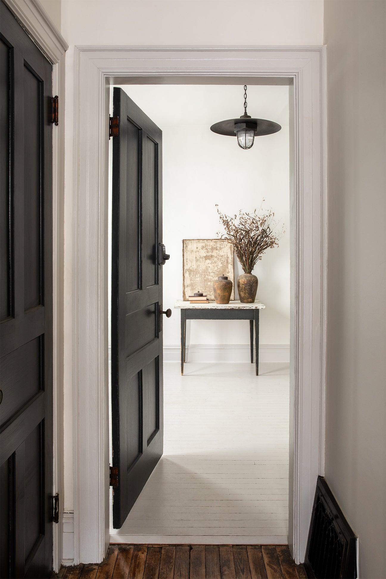 white hallway with black door