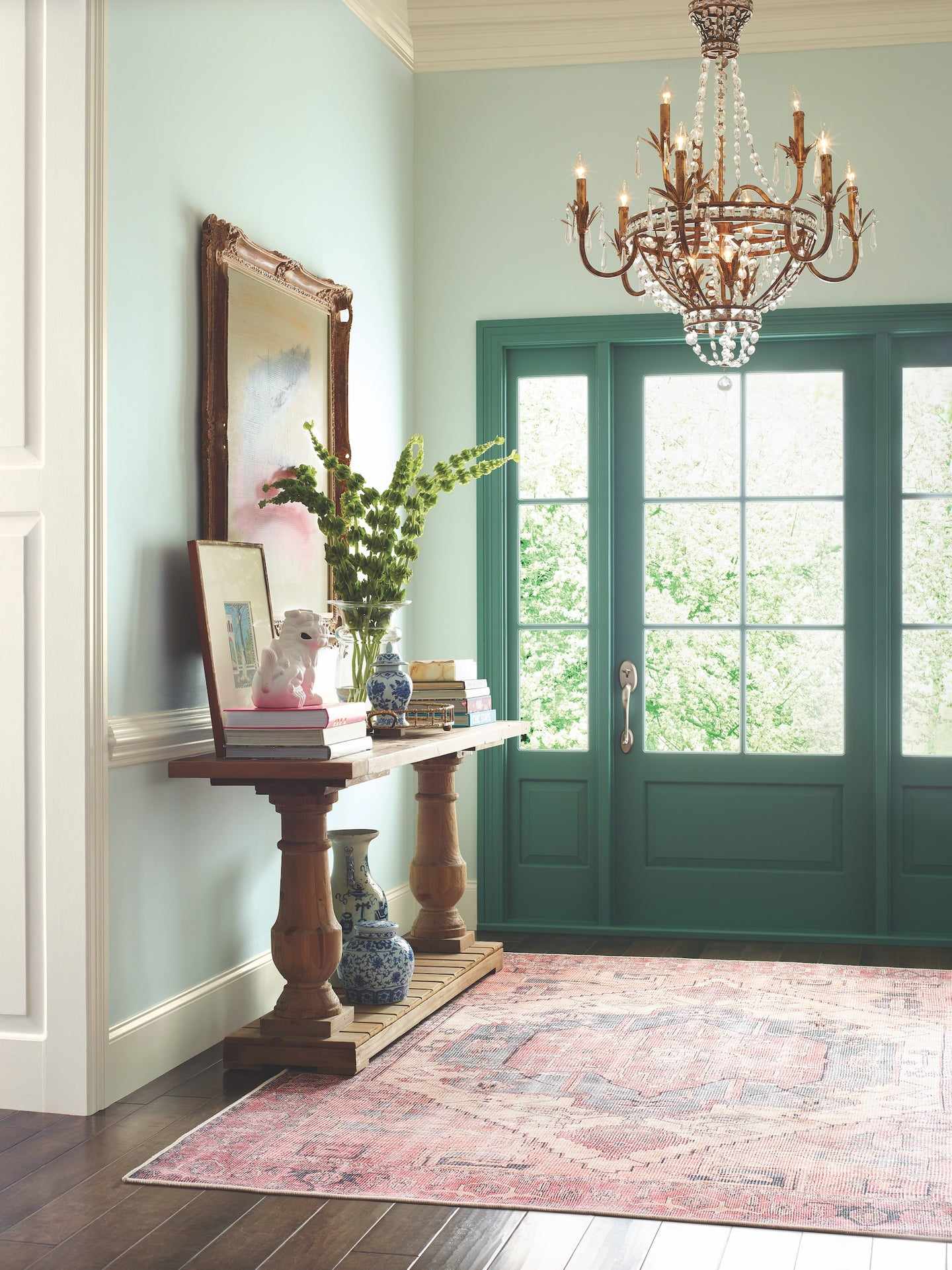 green entryway with chandelier