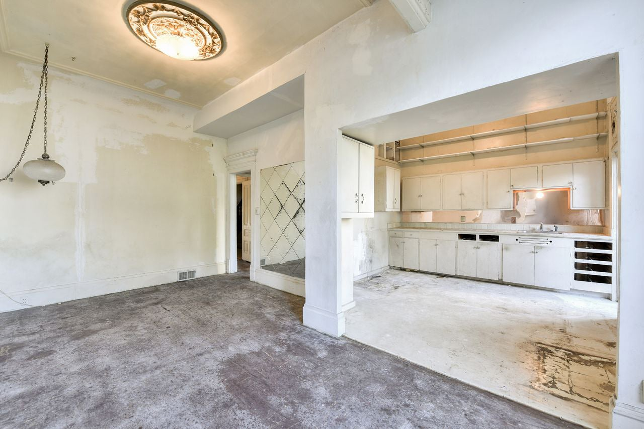 dated white kitchen off a dining room