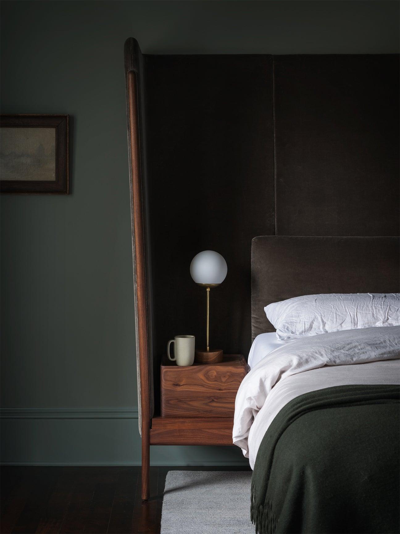 dark moody bedroom with wood headboard