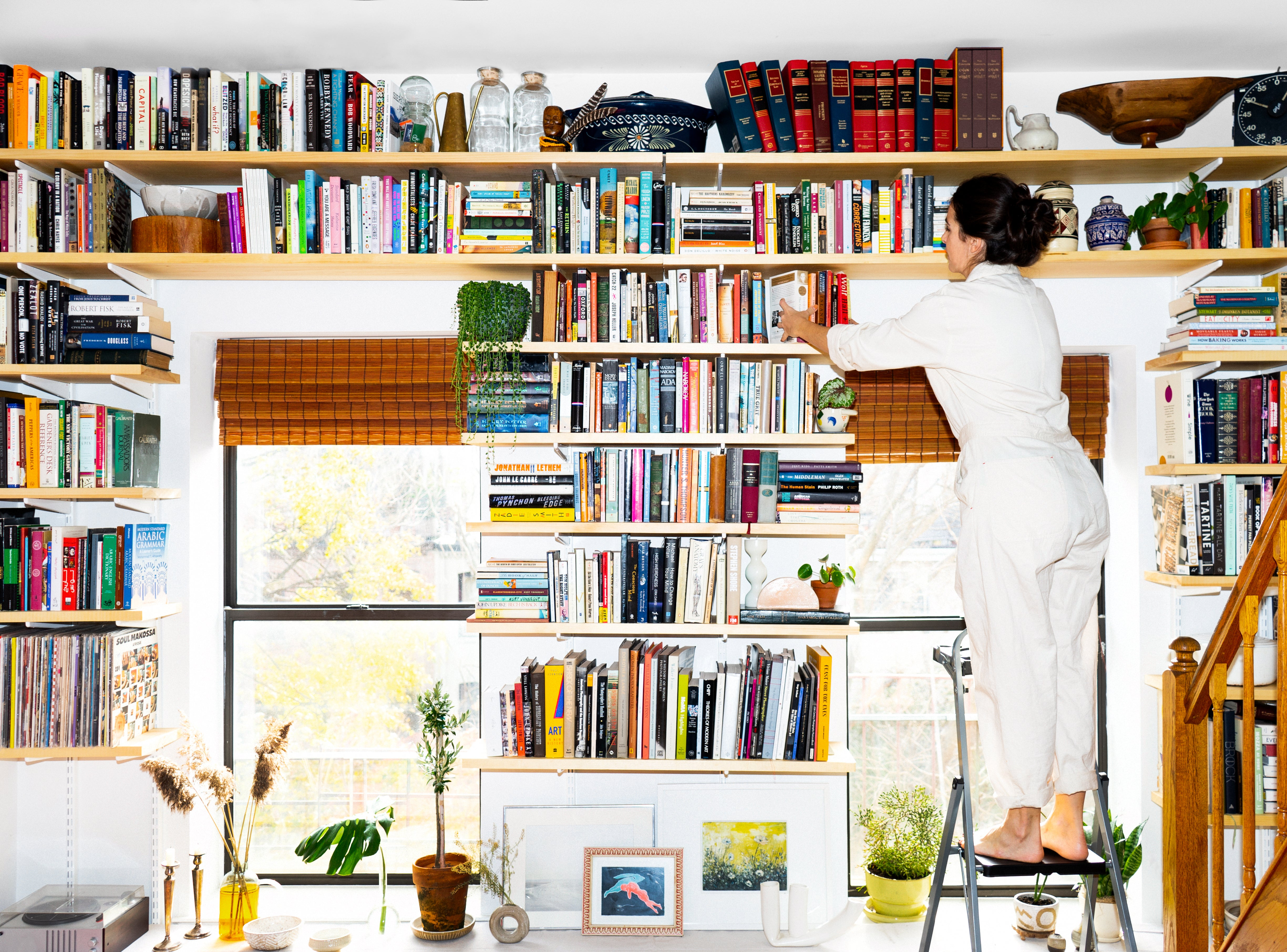 woman on a ladder arranging books