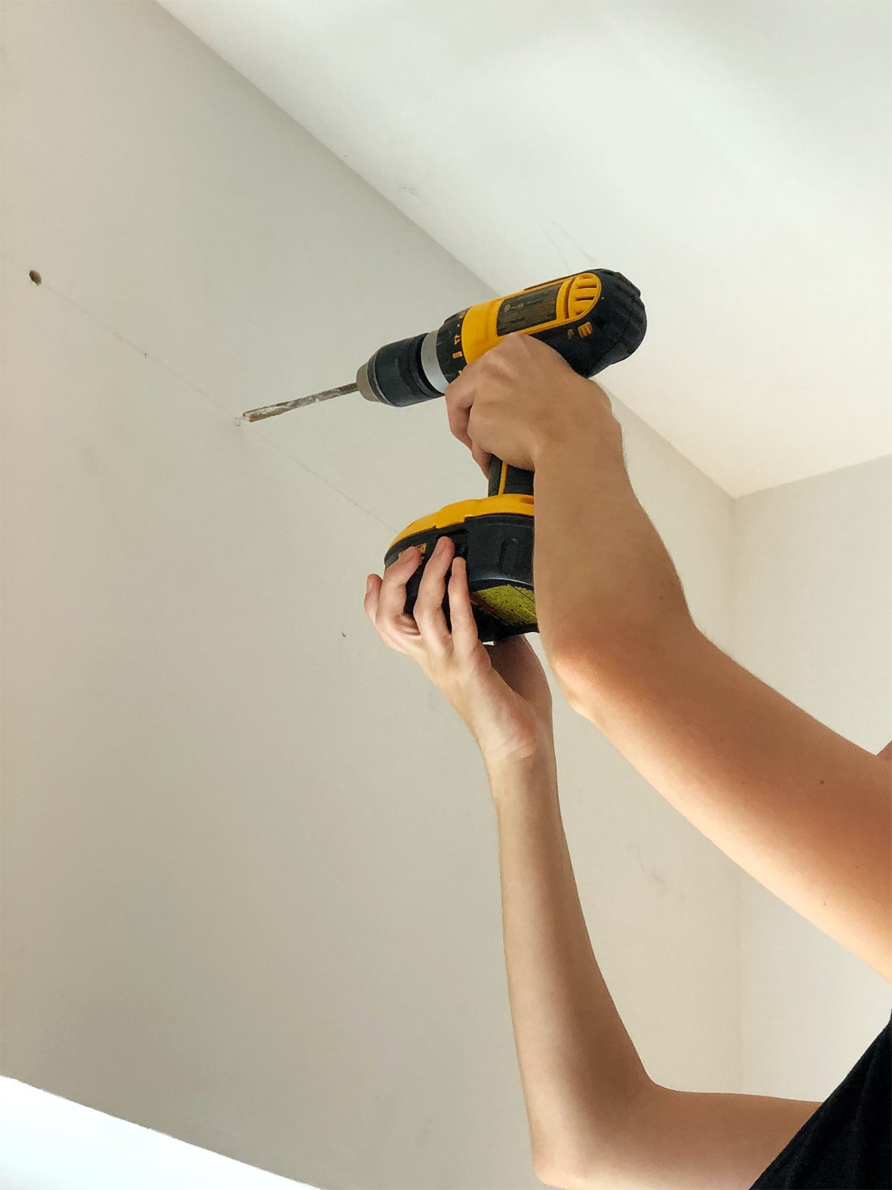 person drilling holes in wall