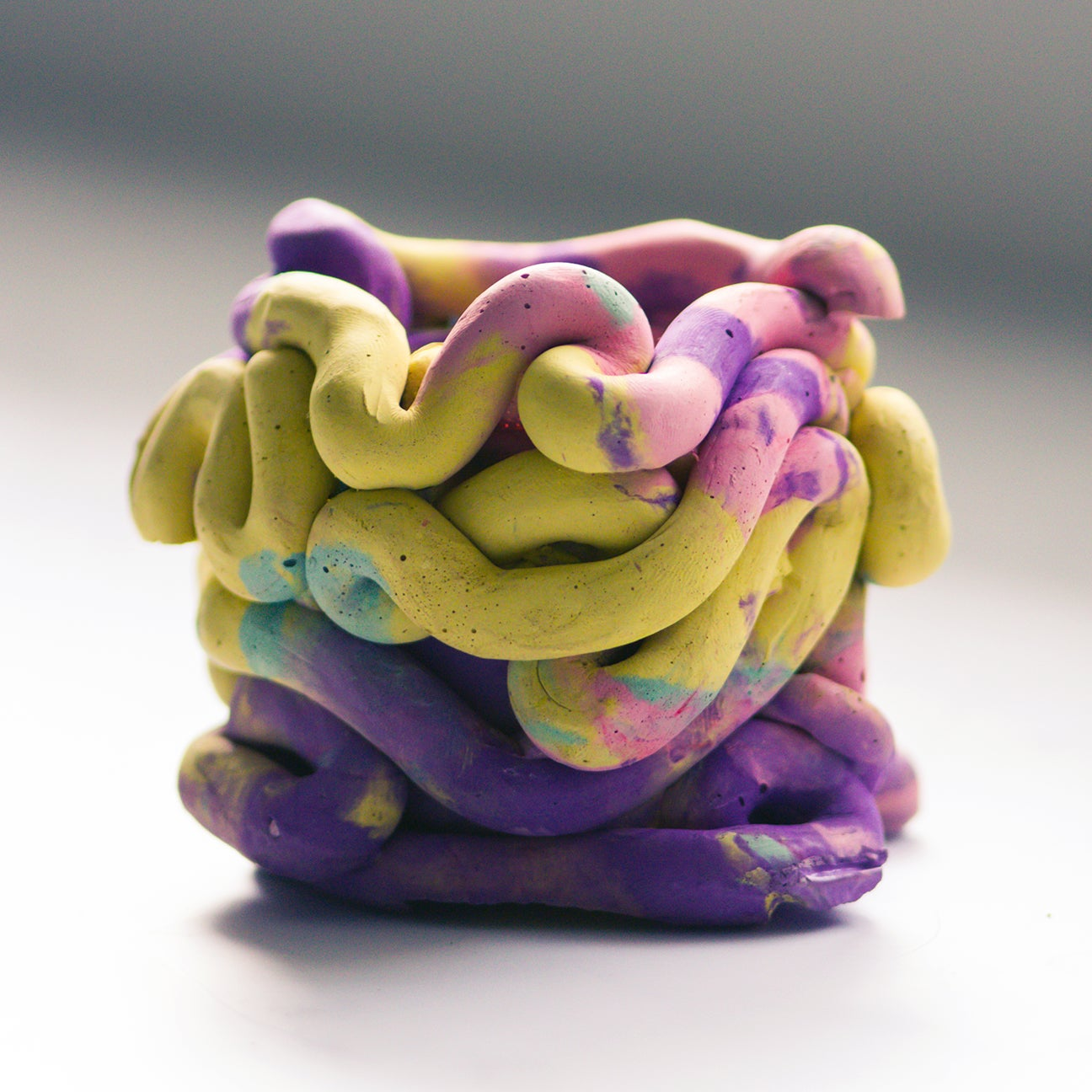 yellow pink and purple vase made up of squiggly parts