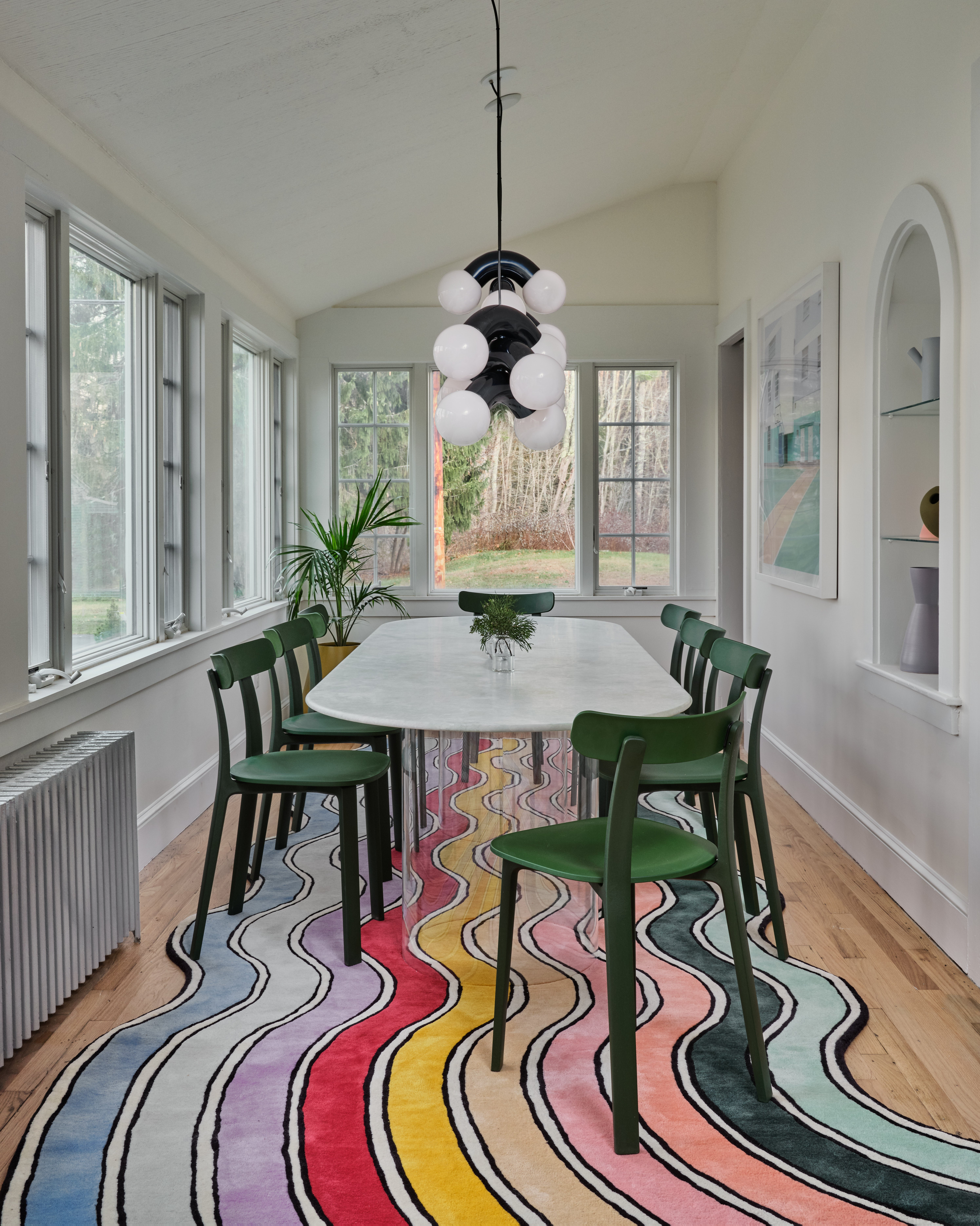 rainbow rug and dining table on it with green chairs