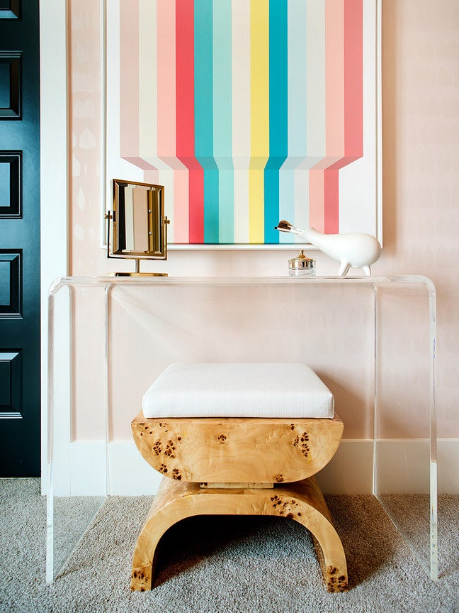 pink room with a vanity and burl wood stool