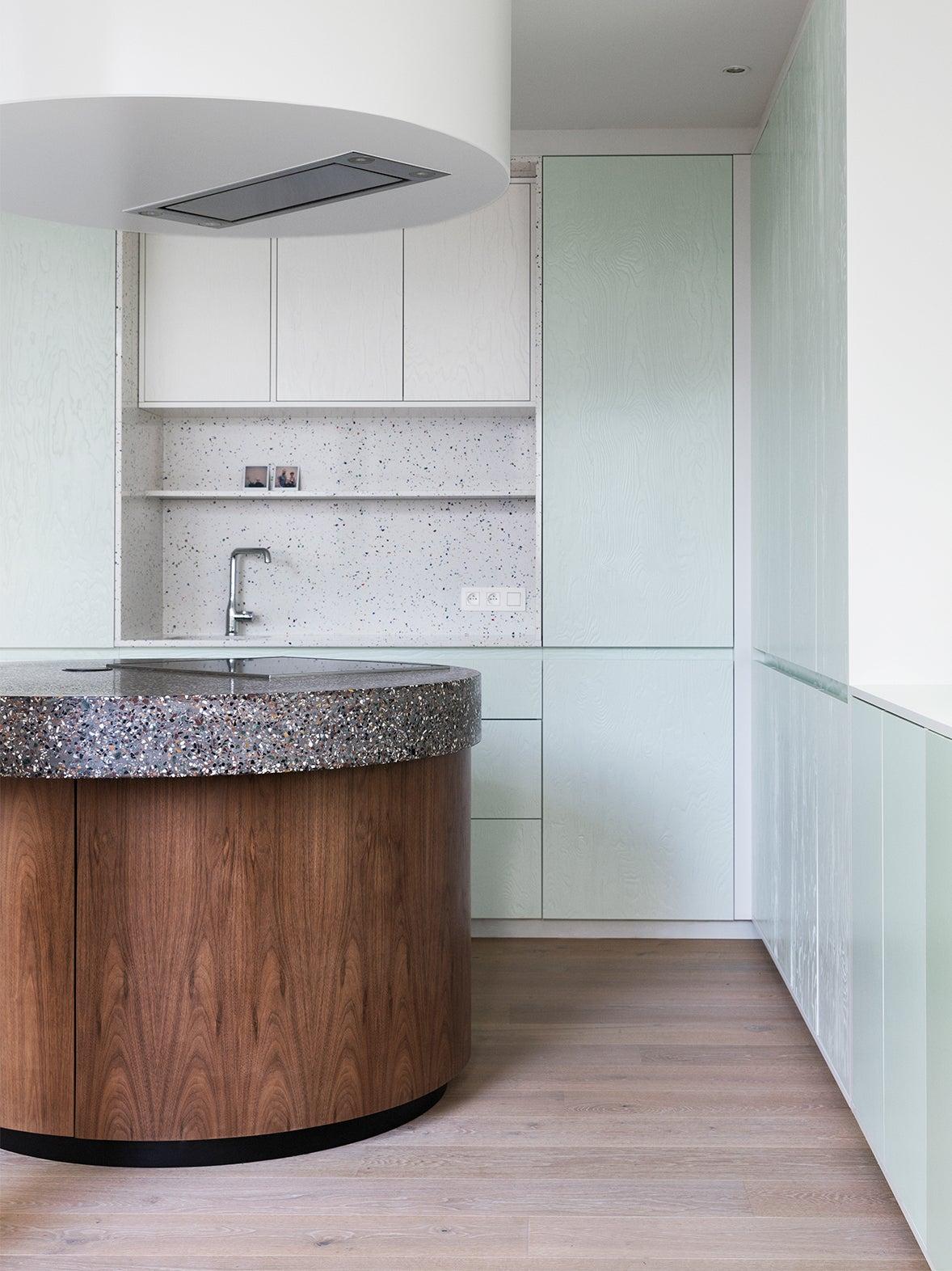 circular terrazzo island withe blue kitchen cabinets
