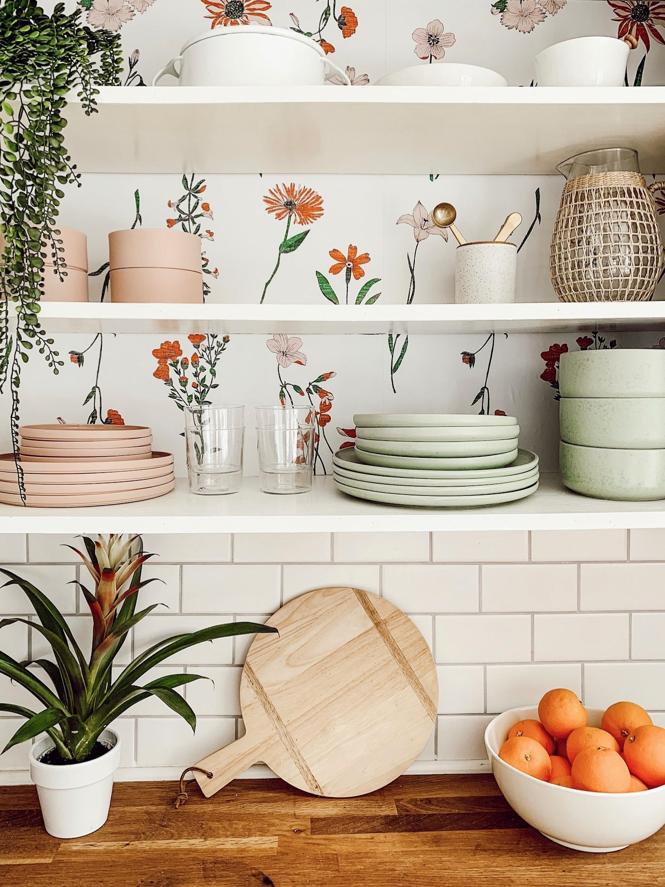 open shelves with wallpaper floral design and mint and pink plates