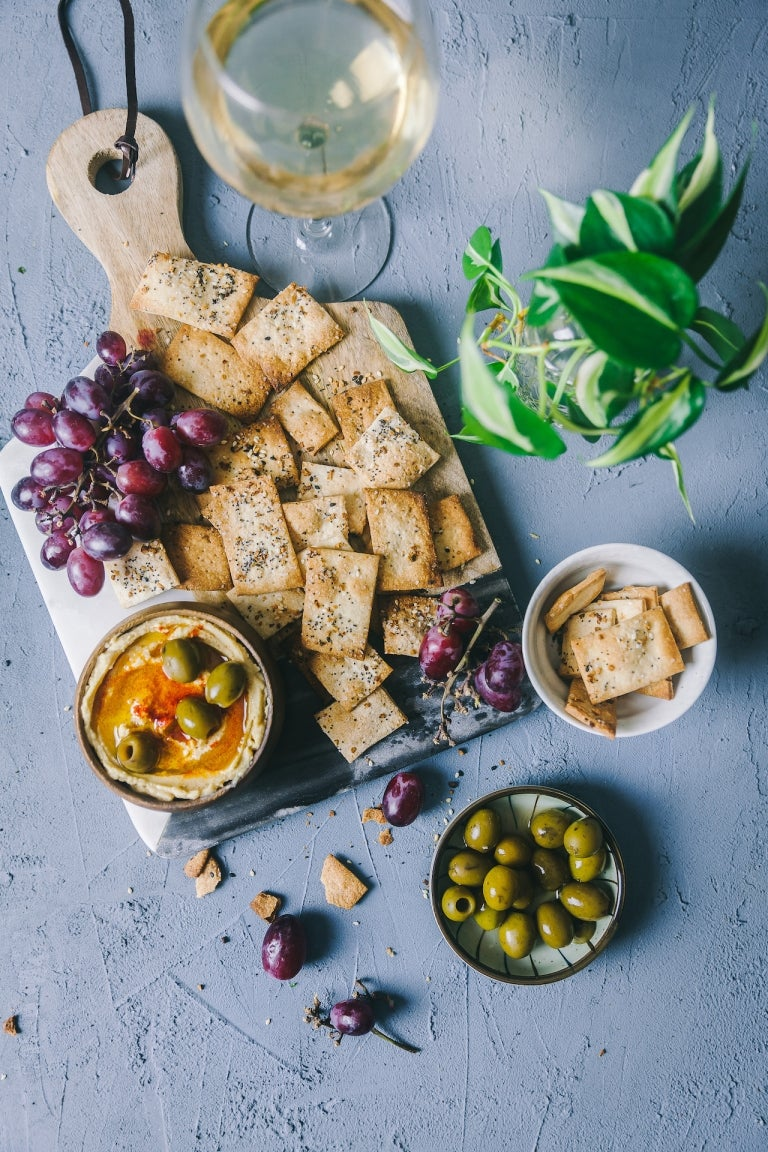 homemade crackers on a board with grapes