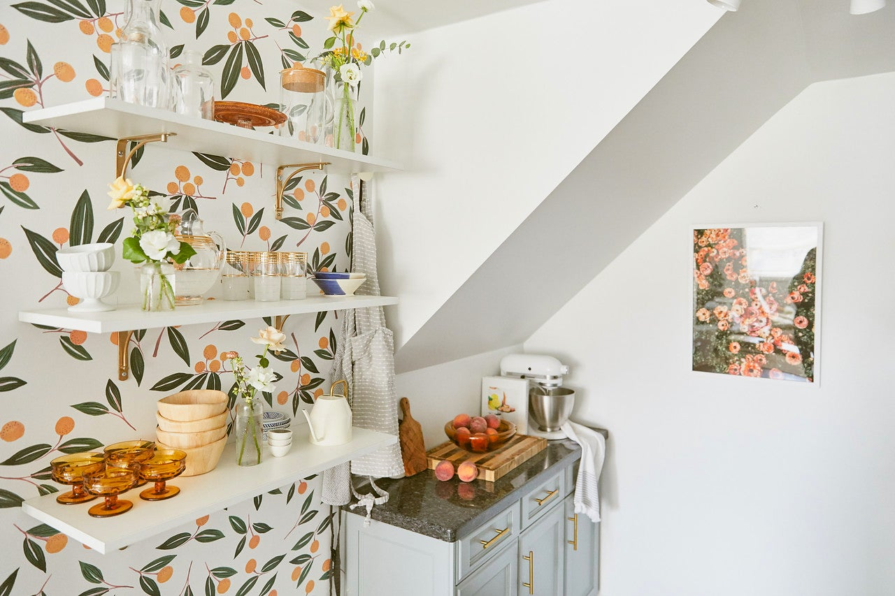 tangerine wallpaper with open shelves and small counter nook