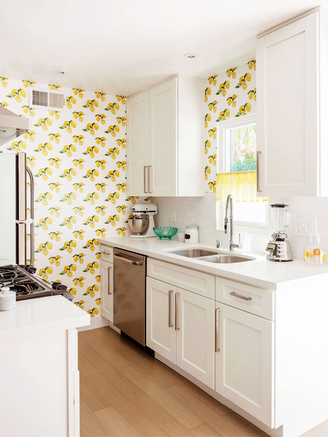 white galley kitchen with lemon wallpaper