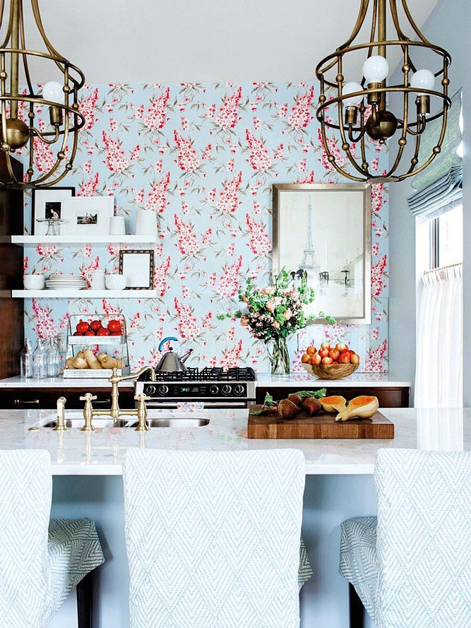 bar stools overlooking kitchen with pink and blue wallpaper wall