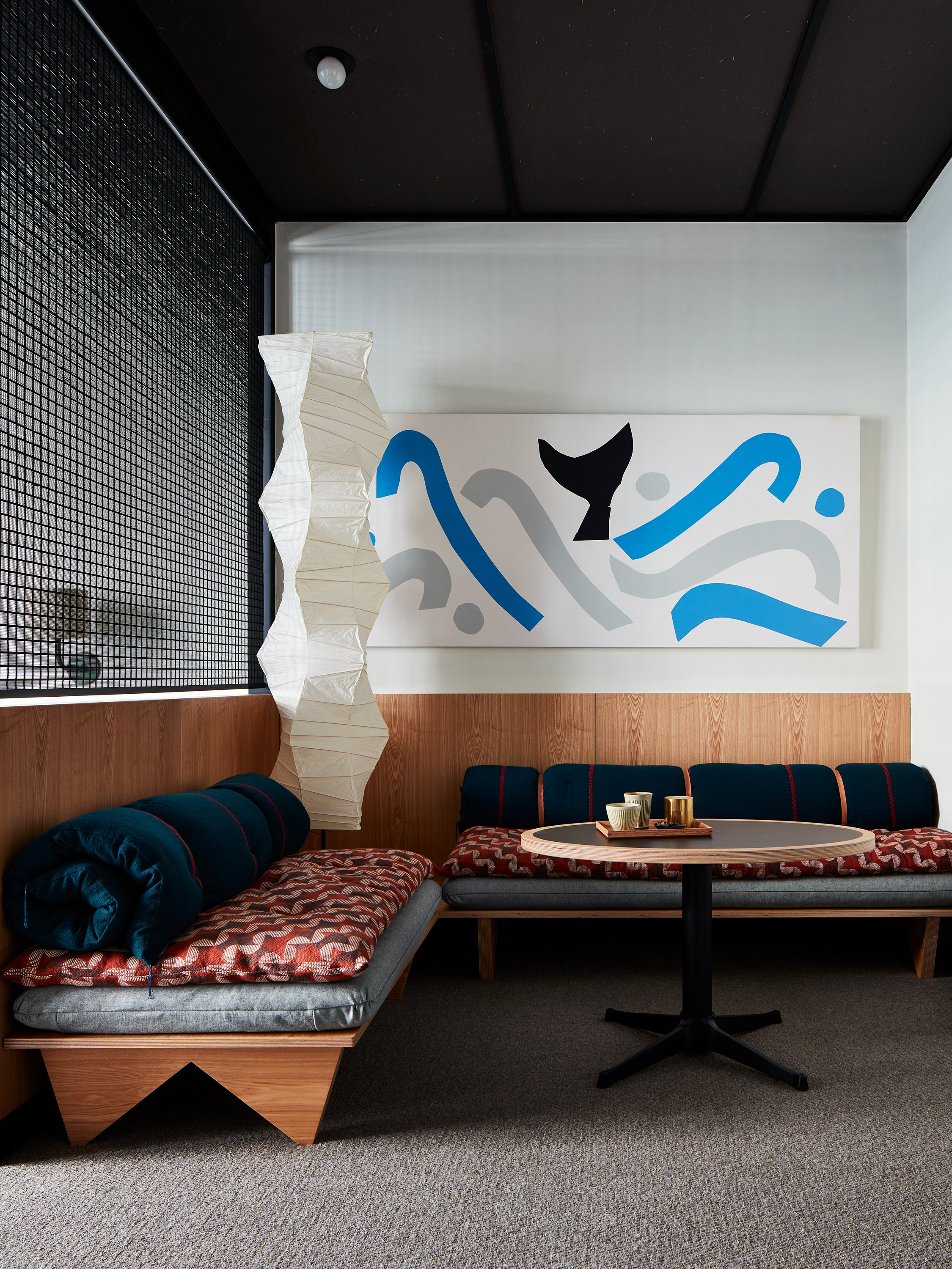 two couches in a corner with large abstract art on wall
