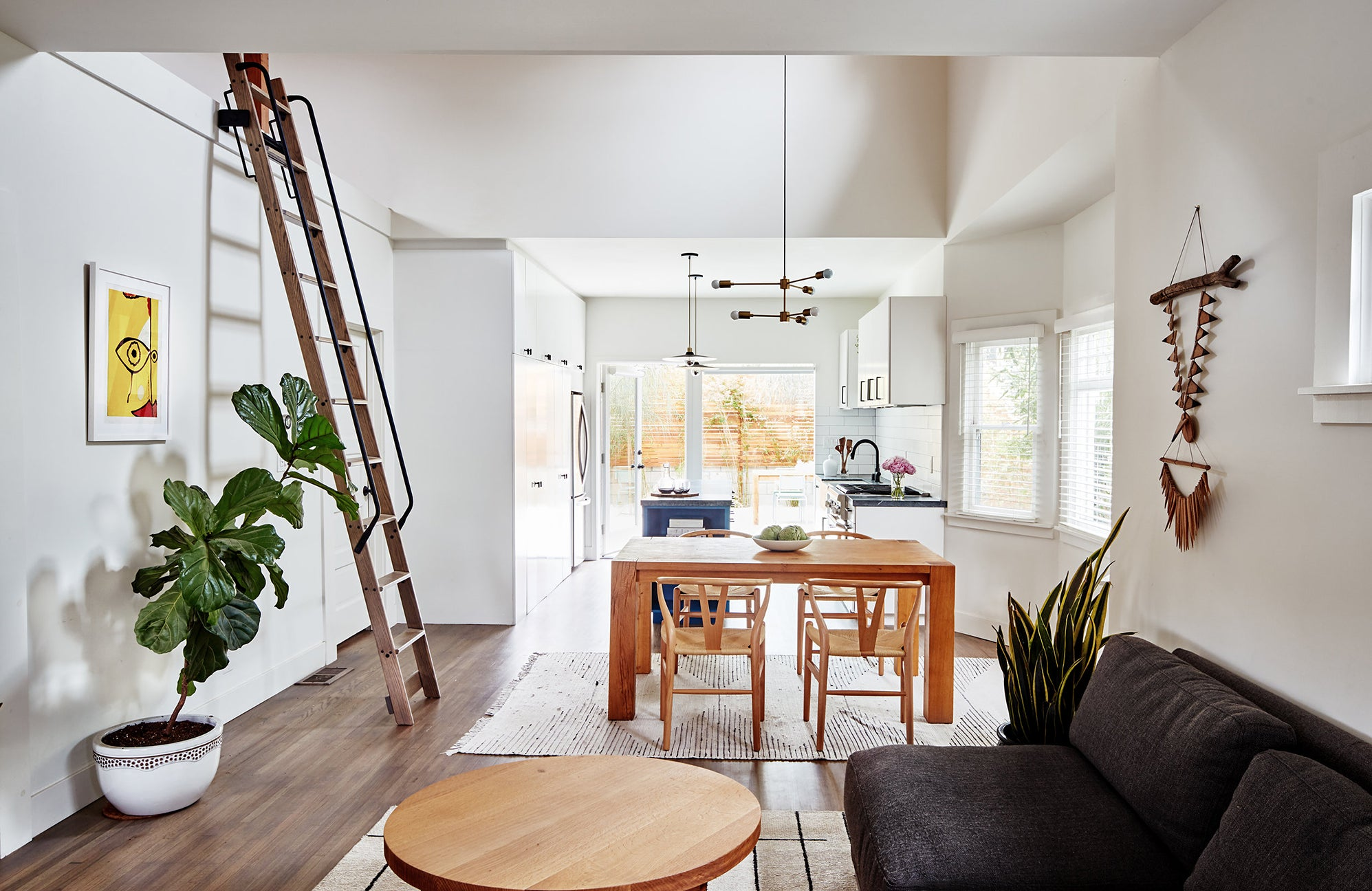 open cnept dining and kitchen and living with ladder on the wall