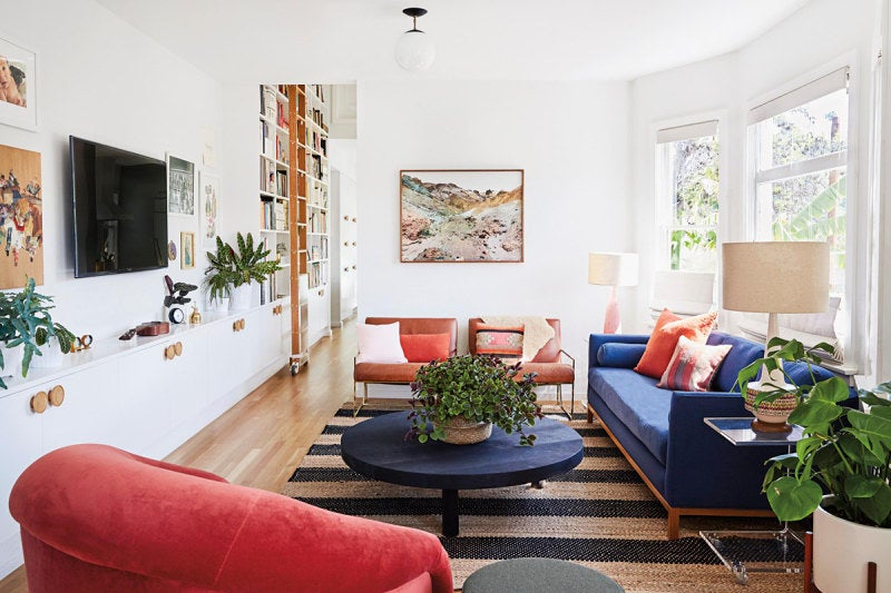 striped living room rug with blue and red sofas