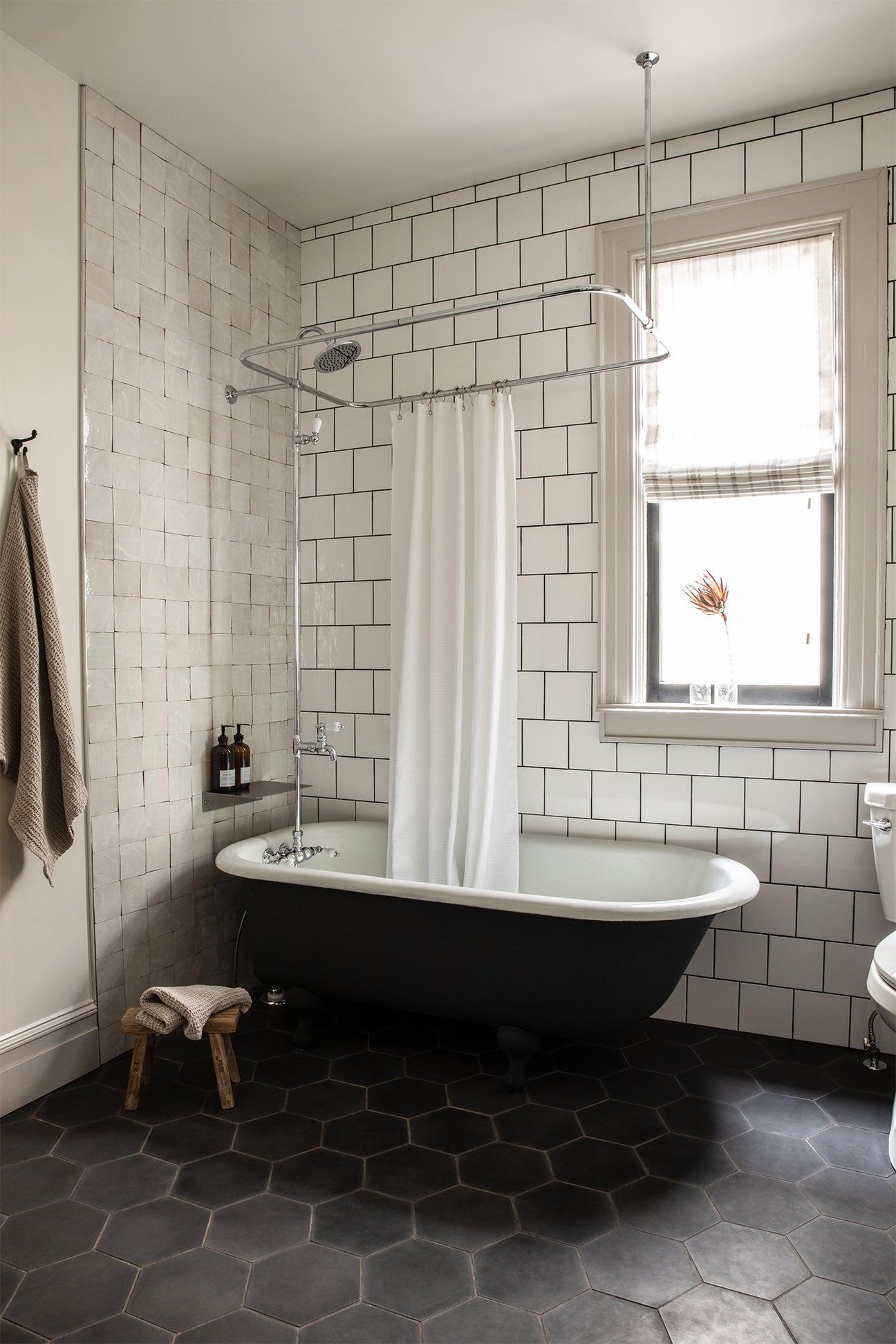tiled bathroom with claw foot tub