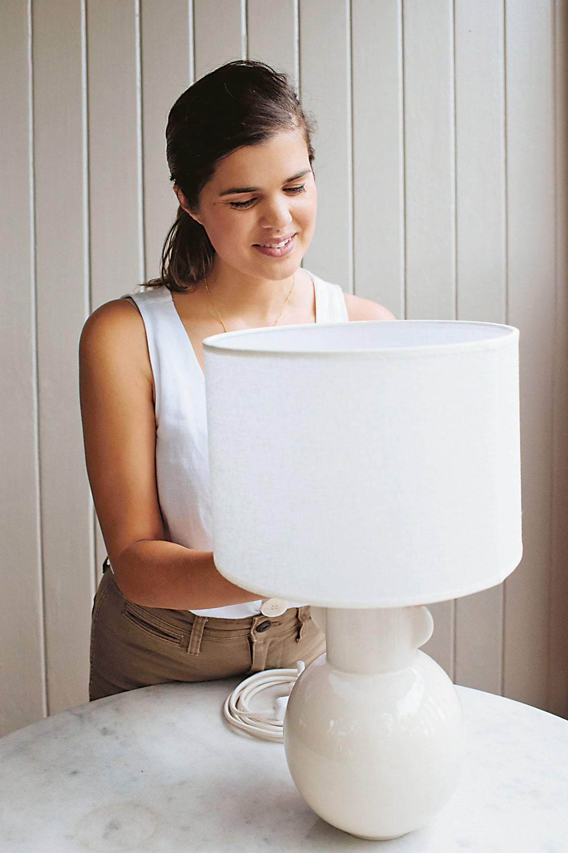 woman putting on a lamp shade
