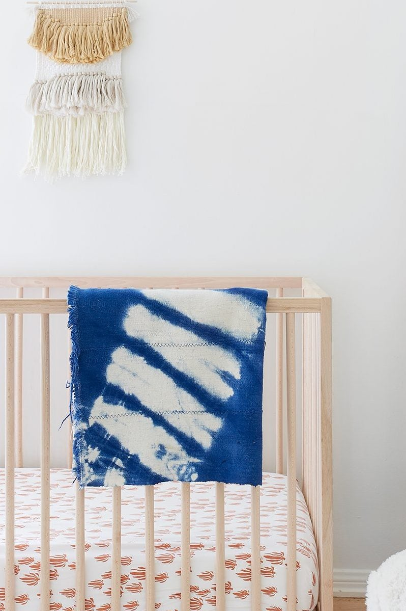 wood crib with blanket draped over