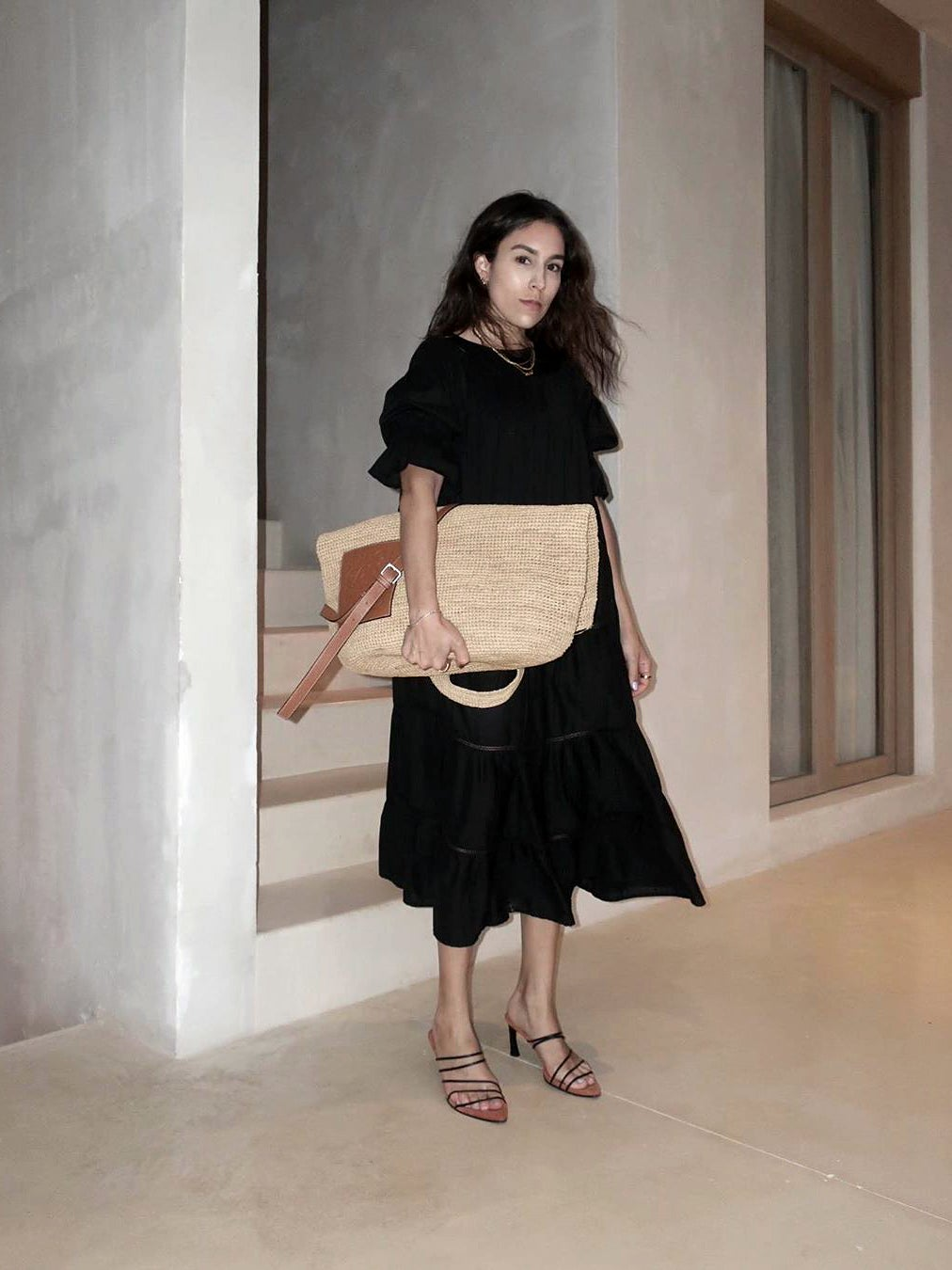 woman in black dress and straw bag