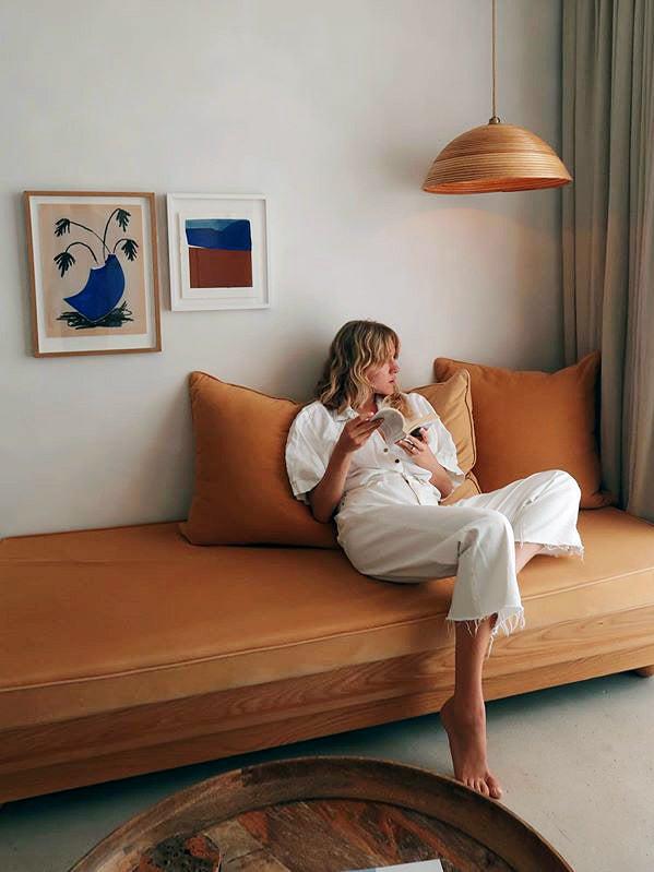 woman sitting on orange sofa