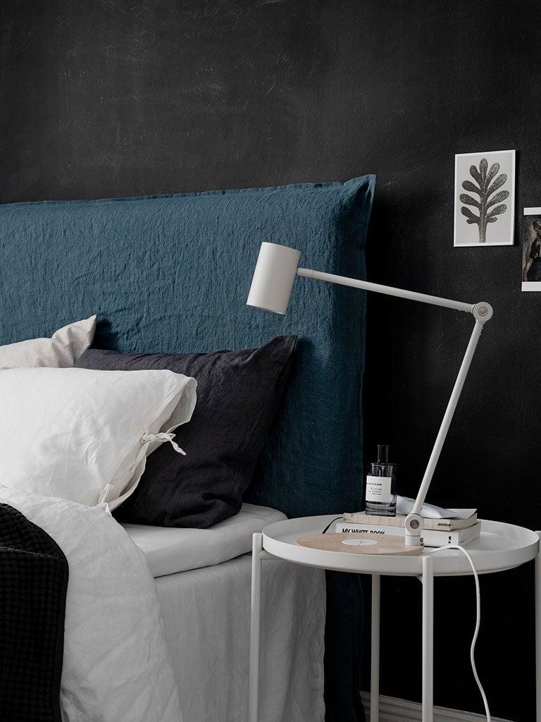 black bedroom with blue linen headboard