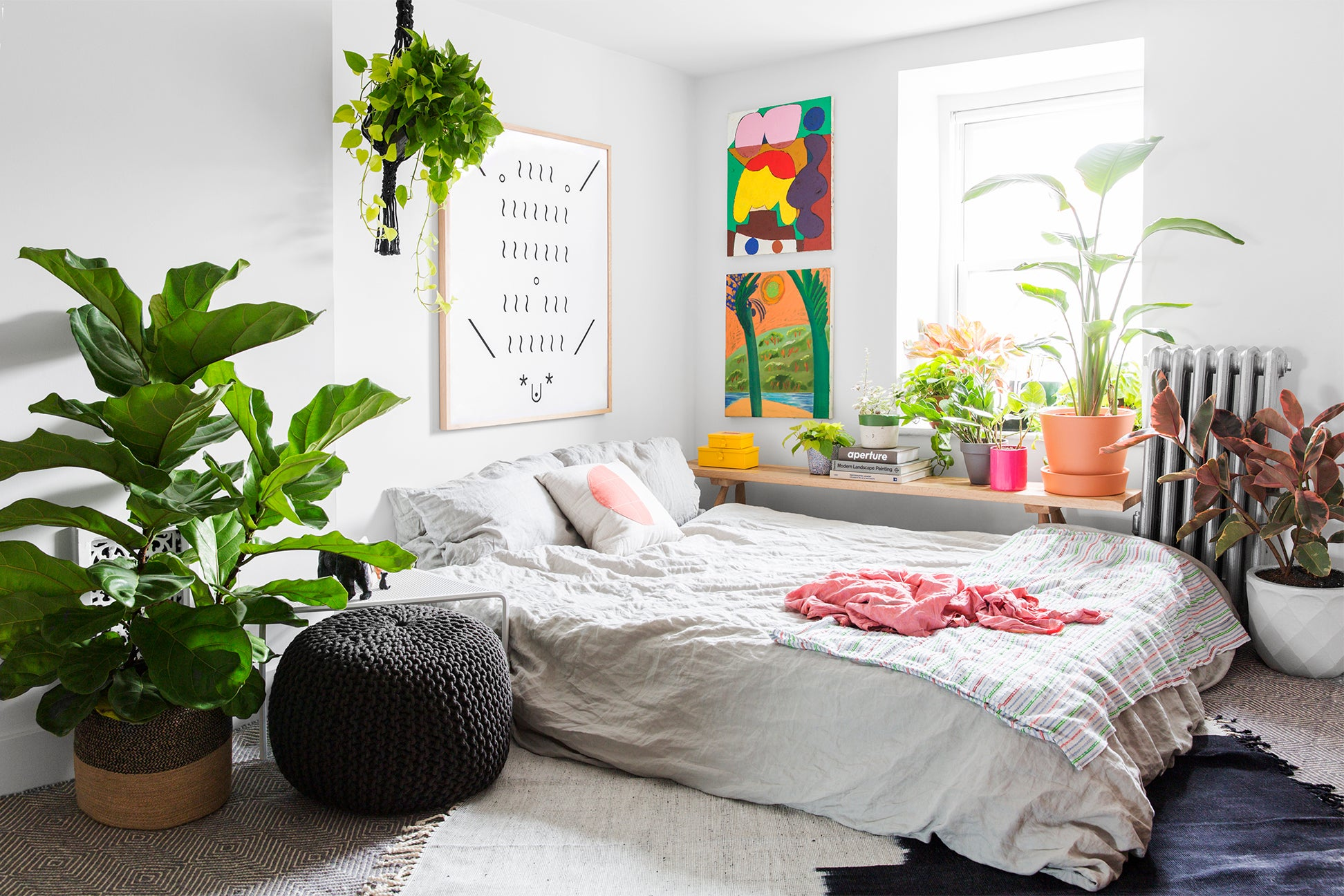 bedroom with lots of plants and rainbow artwork