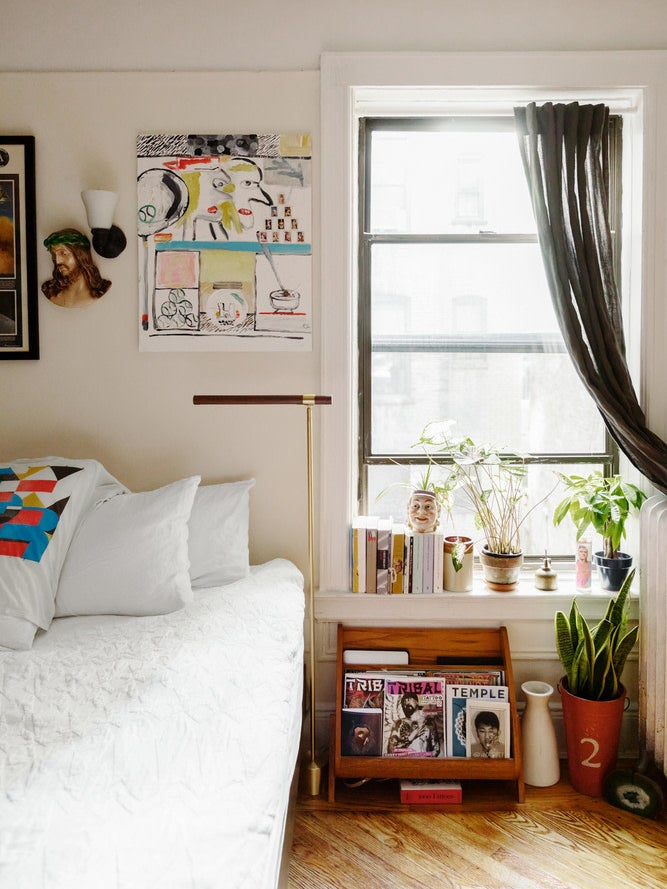 bed with white bedding and books on windowsill