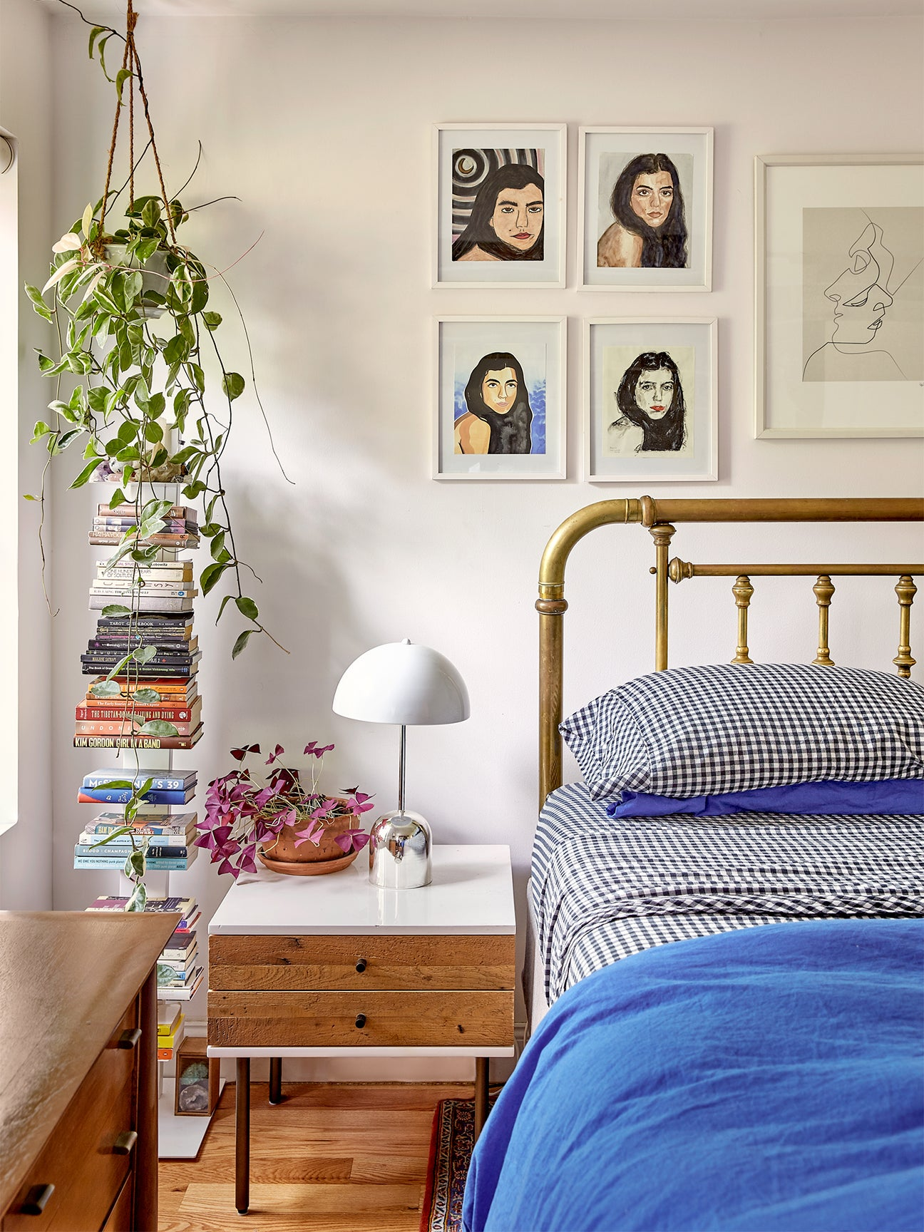 bed with blue sheets, hanging plant, and gallery wall